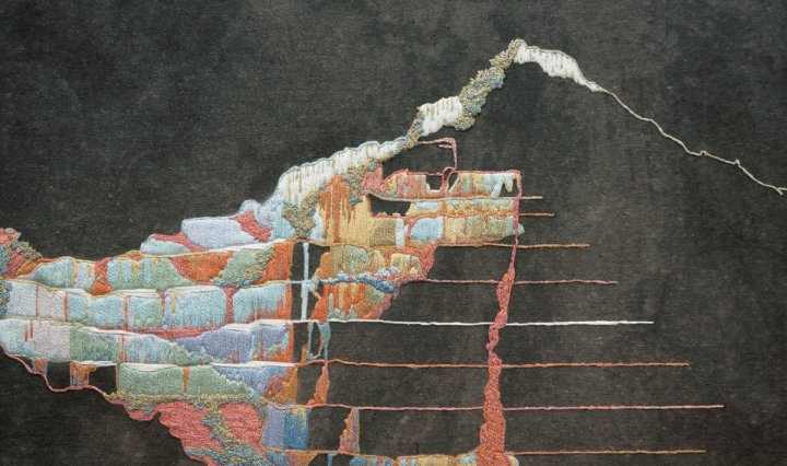 The album cover is an embroidered, multicolored brick that forms into a silhouette of a mountain top with a black watercolor background.