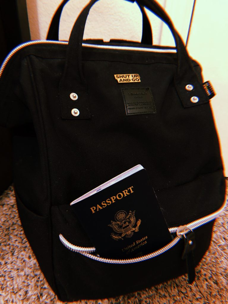 A black backpack with a gold pin and passport sticking out.