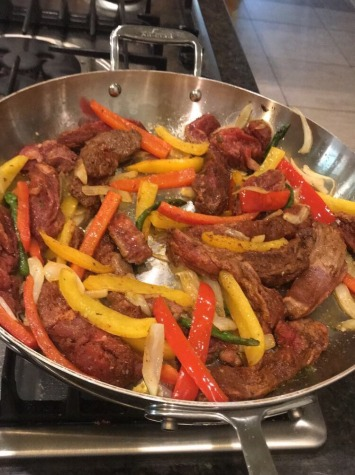 Steak, red and orange bell peppers in a pan.