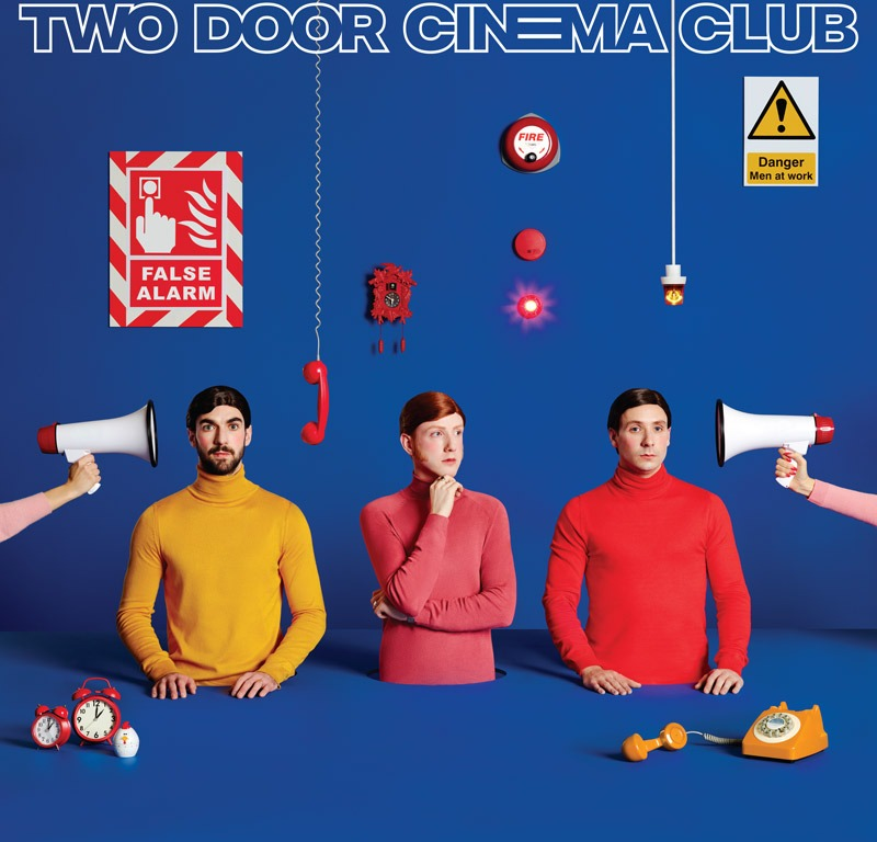 A bright blue background with the three band members in the foreground, each wearing different colored solid shirts. There are various signs on the wall behind them and there are bullhorns being pointed at their heads.