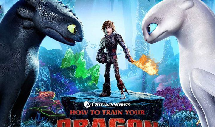 Hiccup, the protagonist of the film franchise, is standing in a blue cave surrounded by gemstones and glittering jewels. He is in full leather armor and holding a sword that is aflame. In the foreground, two dragons, Toothless and the Light Fury, are making intense, unbroken eye contact.