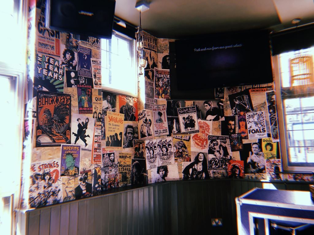 A wall in a London hostel with pictures of rock album covers.