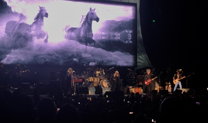 Horses running on the backdrop screen, 6 people playing instruments and singing on stage.