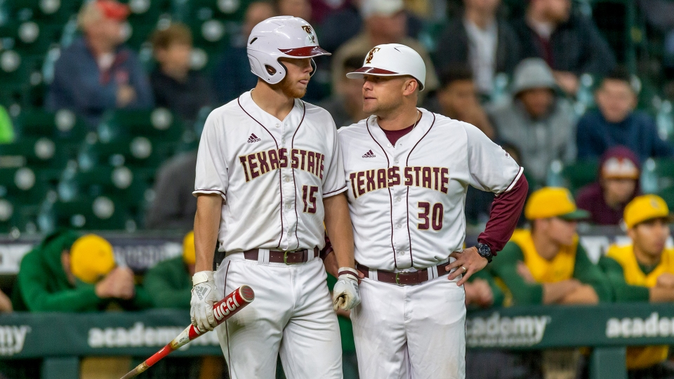 New Texas State baseball head coach Steven Trout speaks with outfielder Chase Evans in between his plate appearance during the Bobcats matchup against a non-conference opponent.