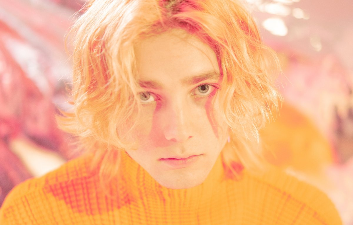 he album cover is a headshot of Instupendo. He's wearing an orange fitted turtleneck and has blonde hair. Behind him is a pink and silver backdrop.