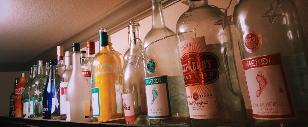 Multiple empty liquor bottles on top of a cabinet.