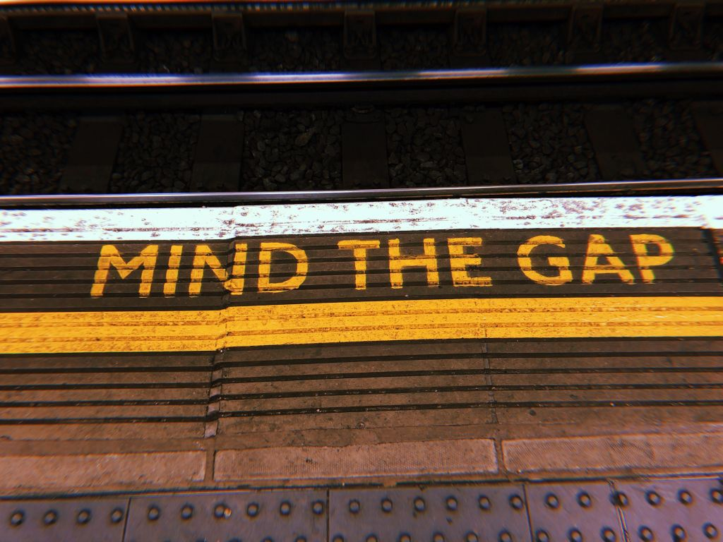 """A photo of London's iconic """"mind the gap"""" floor writing in the underground tube station."""