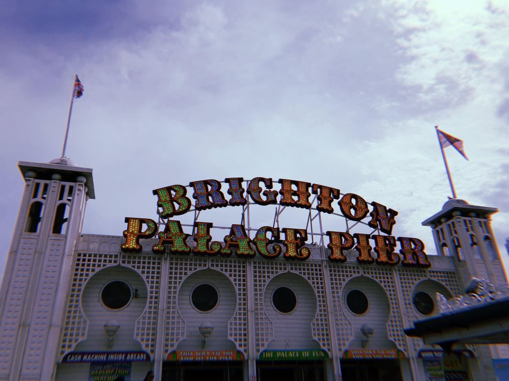 A photo of Brighton Palace Pier's colorful light up sign.