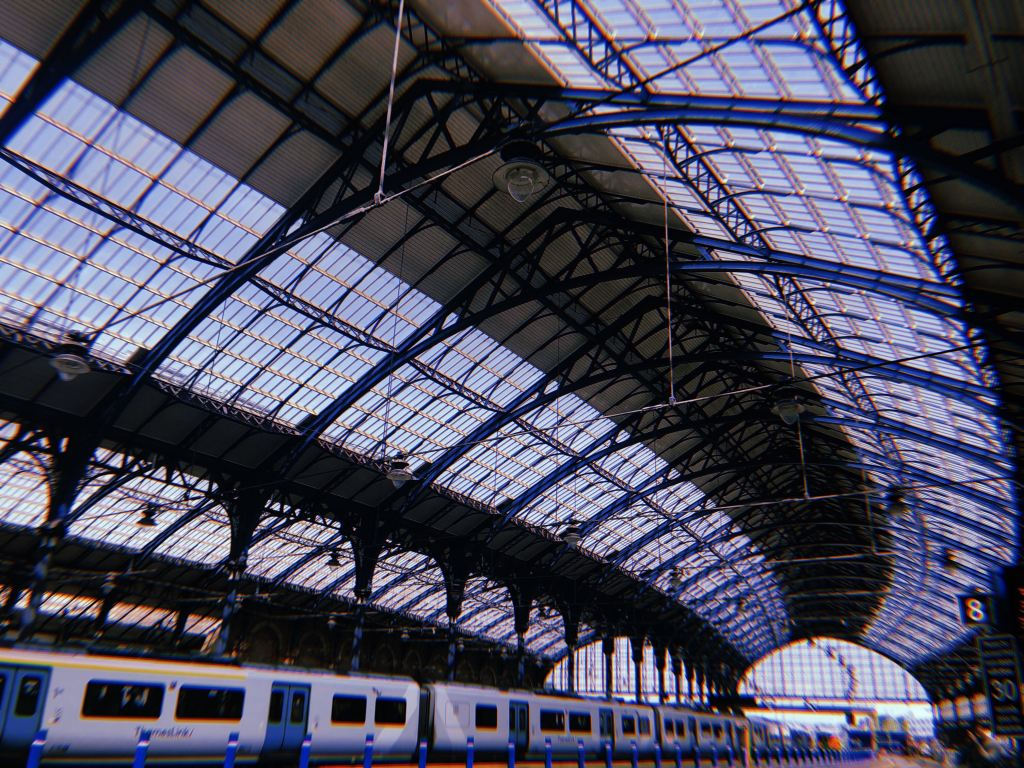 A photo of Brighton Railway Station with bright glass ceilings and a line of train cars.