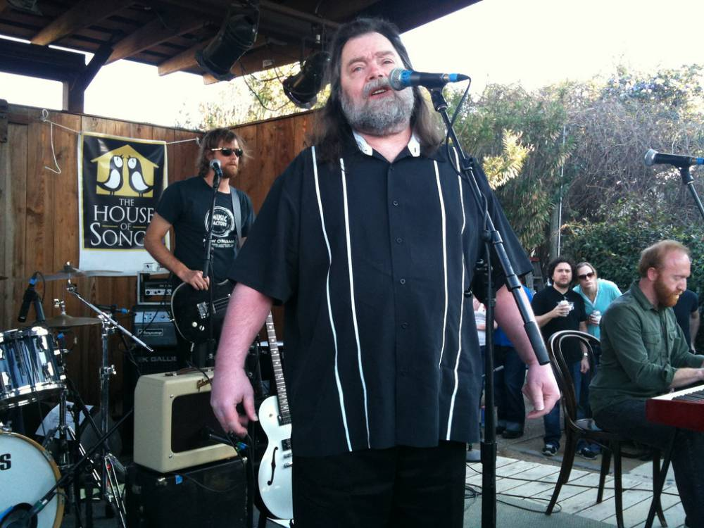 Roky Erickson, singing into a microphone on a small outdoor stage, with a bass player standing behind him, and keyboardist playing to Roky's left, with onlooking concert-goers standing in the background, just off-stage.