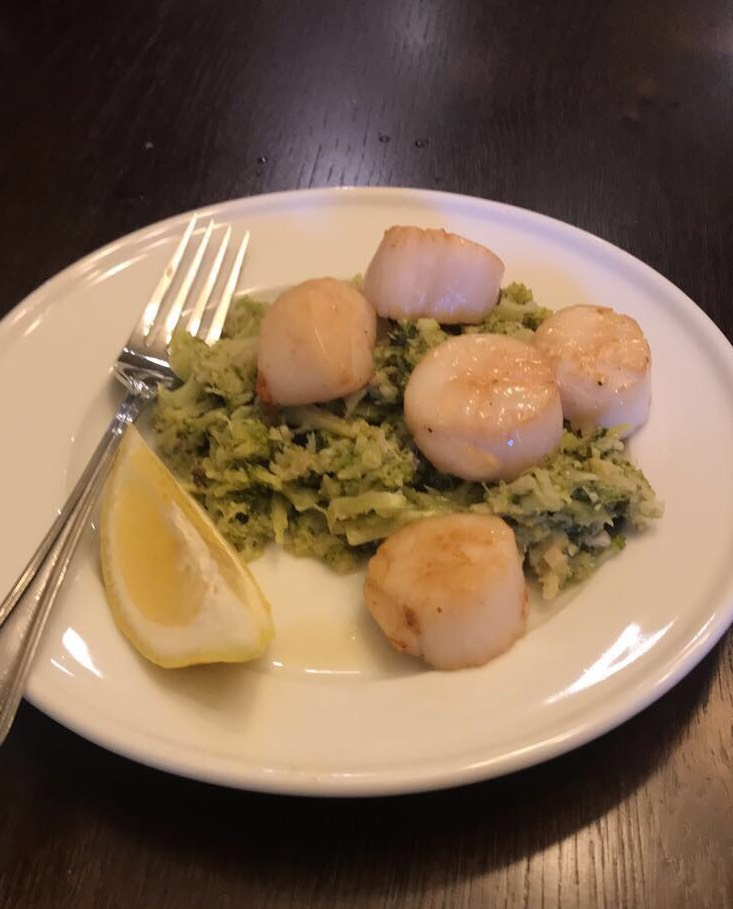 Pan-fried scallops on a bed of broccoli mash with a lemon wedge.