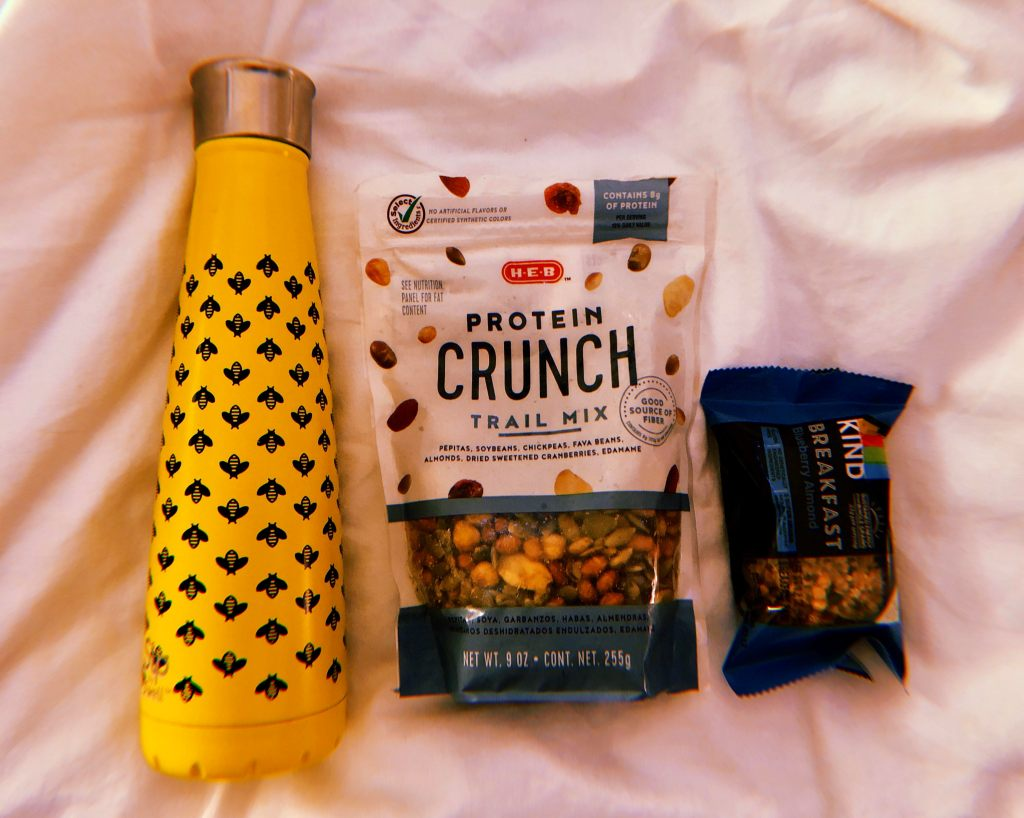 A yellow bee printed water bottle, trail mix from HEB and KIND granola bar.