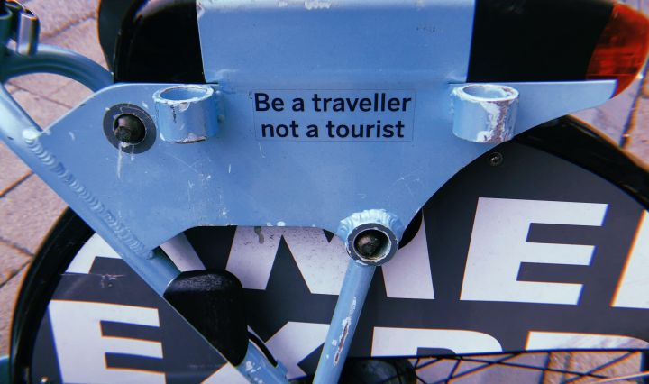 "A sticker that reads ""be a traveller, not a tourist"" on a bike rack. Seen in Brighton, England."