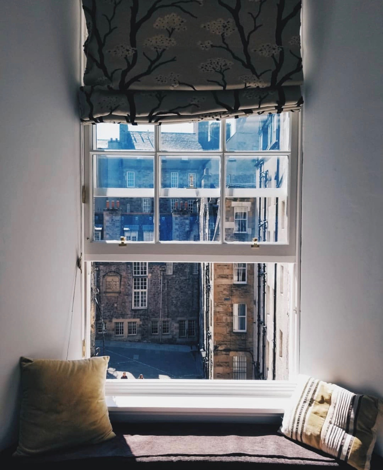 An open window in an Edinburgh flat on a sunny day, with a view into the courtyard and stone buildings across the way.