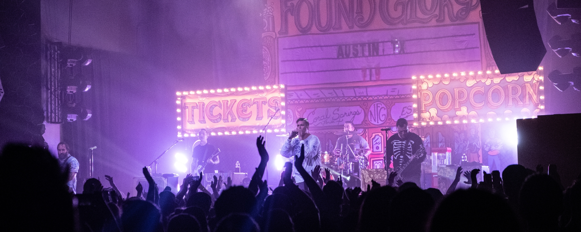 New Found Glory play in front of an audience at Emo's Austin. Behind the band, a big marquee with their name, city and date of the concert.