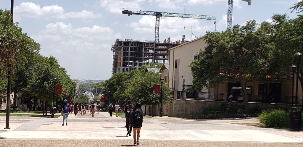 Students walking through the Texas State University campus with a construction site present in the background.