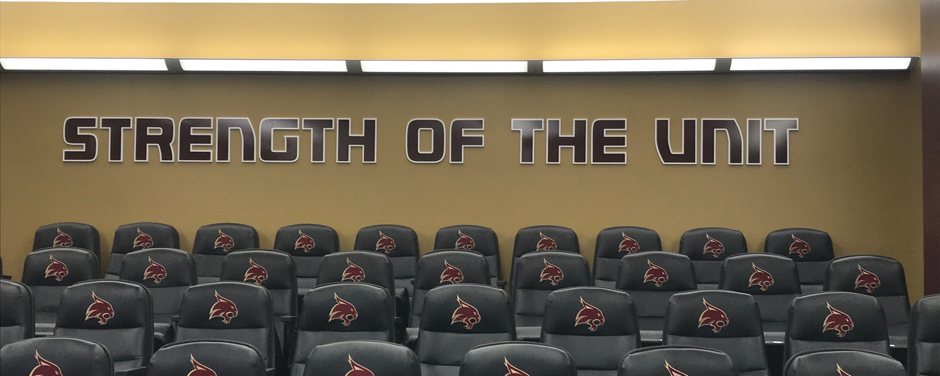 """Strength of the Unit"" is in bold maroon letters at the top of Texas State's press conference room."