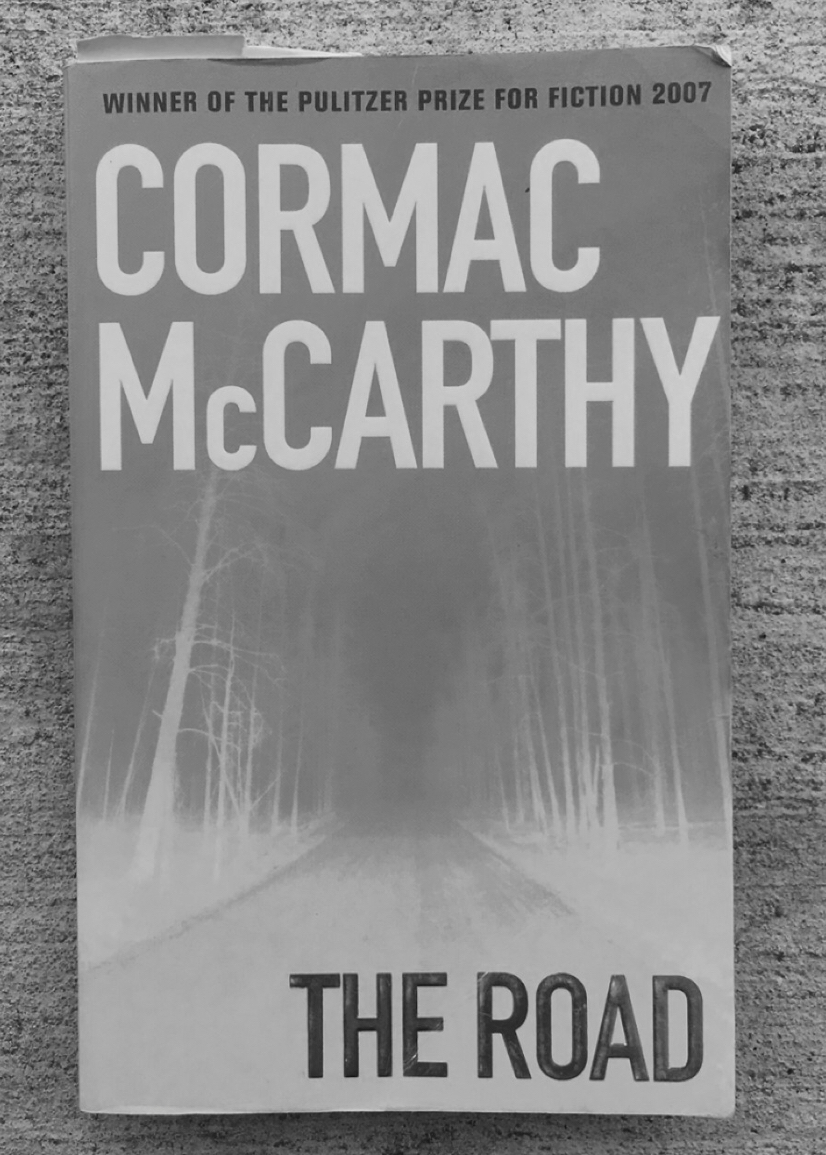 "Image of ""The Road"" book cover on concrete. Edited to appear in black-and-white."