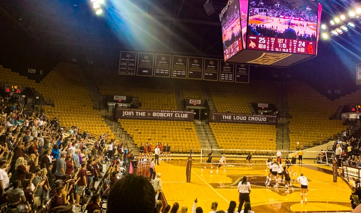 To the left of the picture is the Texas State Bobcat fans all standing to support the women's volleyball team (to the right of the picture) who are battling USC with only one more point that the bobcats need to win the first set. Up top in the picture is the view of the scoreboard which says bobcats have 25 points and USC has 24 points.