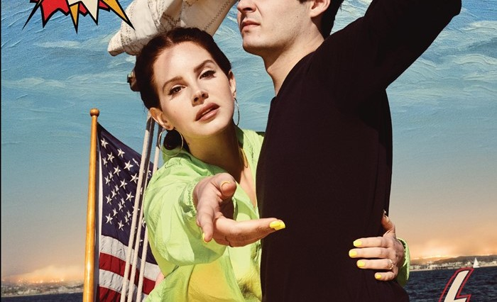 Lana Del Rey reaches out to the camera, a man is next to her looking off to the left, and they are both on a boat.