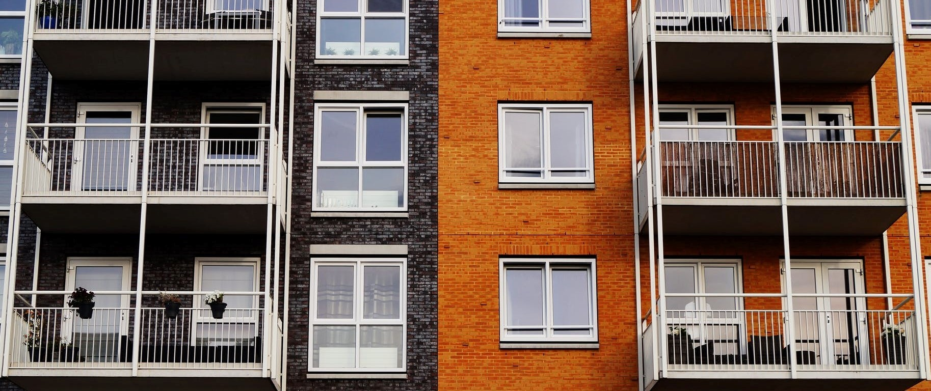 A block of apartment windows and balconies, half on a gray brick wall and half on an orange brick wall
