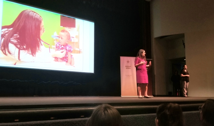 Woman on stage standing in front of a powerpoint projection.