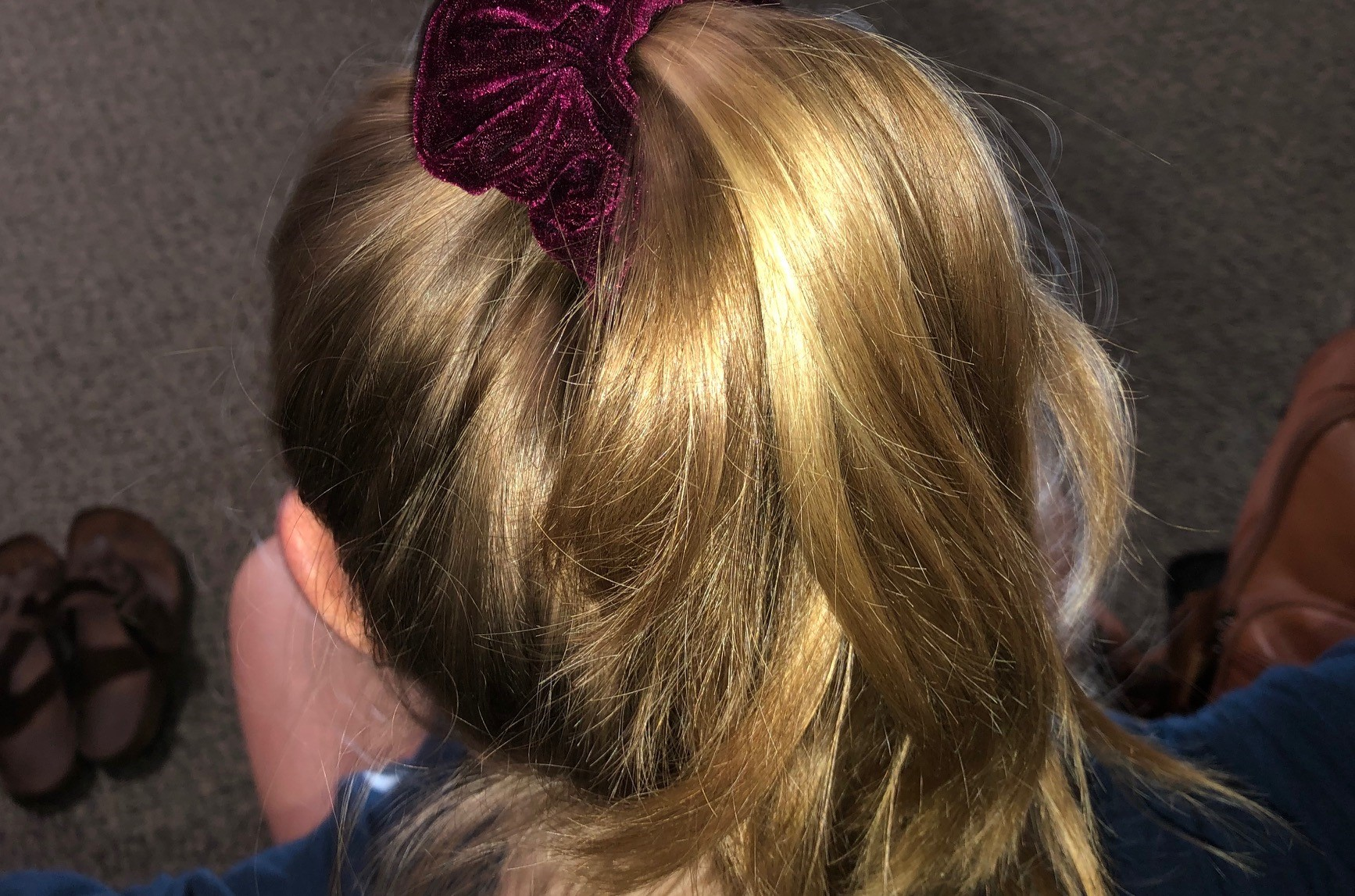 blonde hair pulled back with a maroon scrunchie.