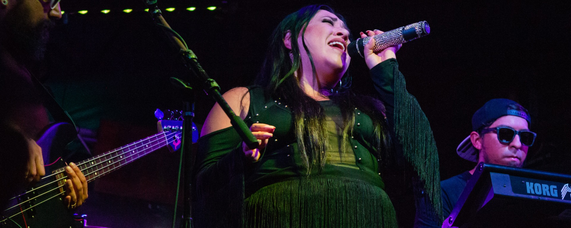 The photo features a woman singing with a microphone in her hand dressed in a black fringe dress