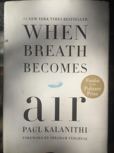 "The Book Cover of When Breath Becomes Air, a White Background with the Words ""When Breath Becomes air"" on the Front and a Small Blue Feather"