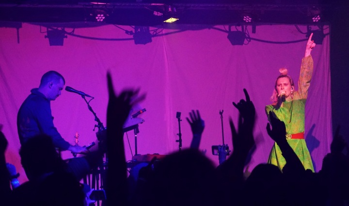 A man on the keyboard is left of frame on a stage while a woman in a green dress holds her left arm up while singing. Hands from the crowd frame the bottom of the photo, and the stage is lit with a pinkish hue.