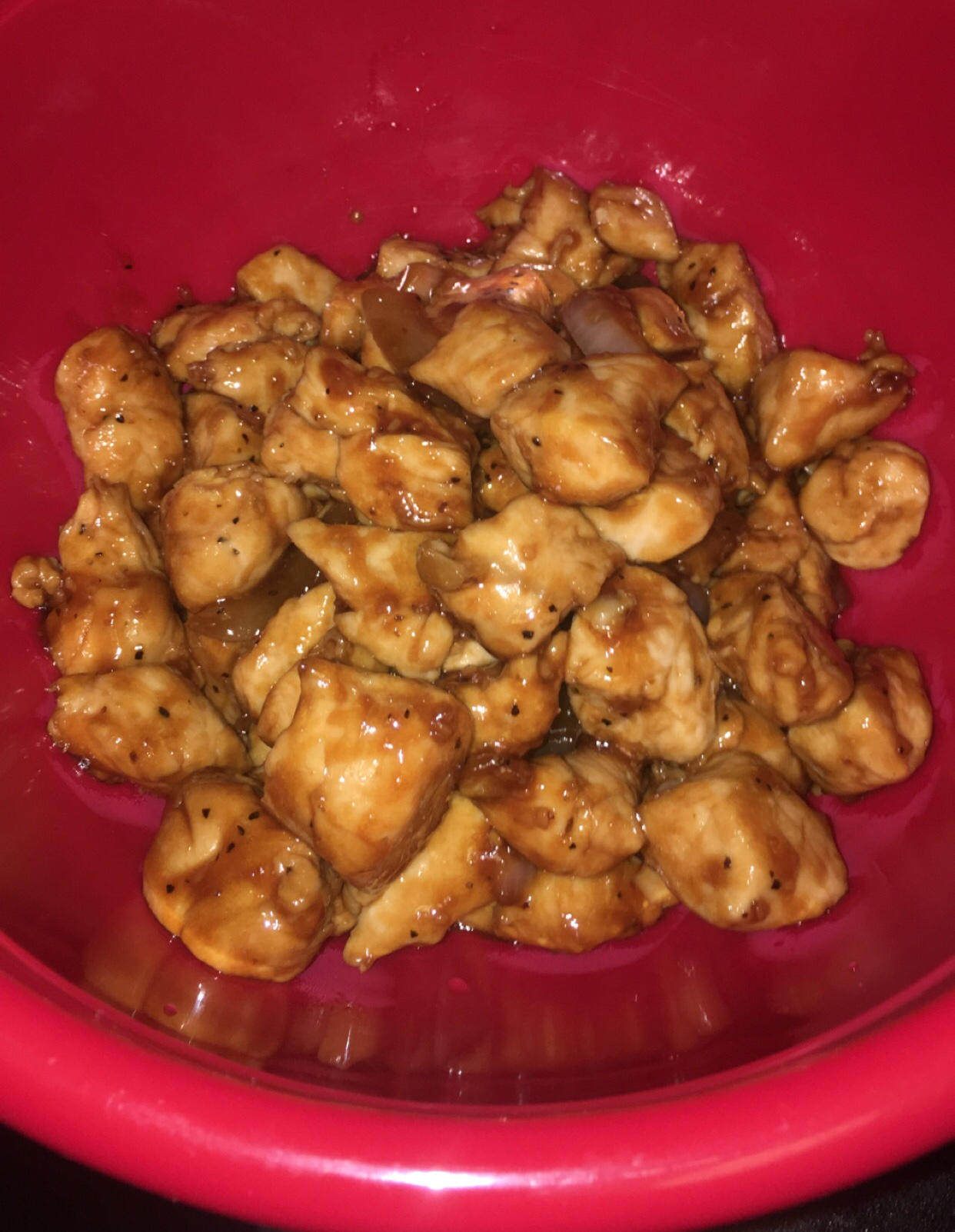 Teriyaki chicken in a red bowl.
