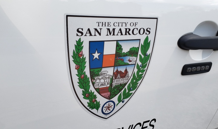 The Seal of San Marcos displayed on the door of a service truck. It features the Texas flag, a river, Old Main, and a gazebo in quadrants.