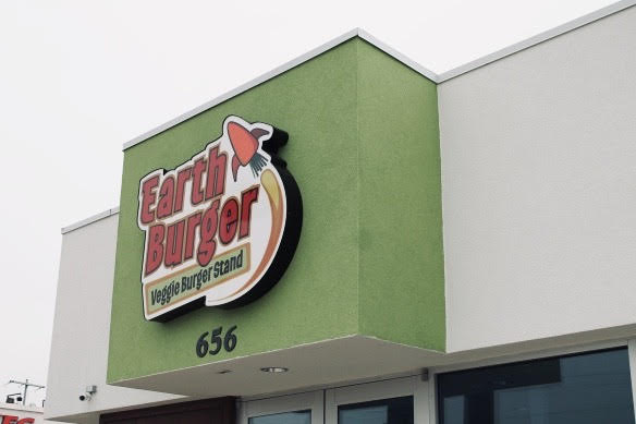 The Earth Burger logo on a green building