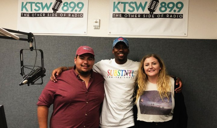 Filmmaker, Russell Reed posing in between Other Side Drive hosts Cheyenne Young (left) and Jozhua Martinez (right), in front of a grey background. KTSW banners are hung on the wall above them.