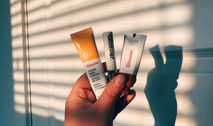 A closeup of three Glossier products held up in front of a door with the shadow from the blinds over it.
