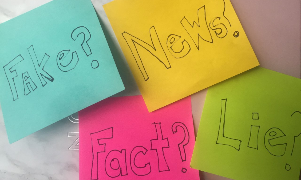 "four colorful sticky notes on a marbled background with one reading ""Fact?"" another ""News?"" another ""Fake?"" another ""Lies?"""