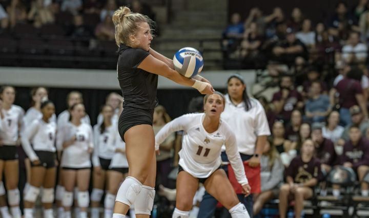 Defensive Specialist Micah Dinwiddie wearing a black libero jersey hitting a volleyball with her forearms towards the opposite side of the net with her teammates and fans looking on.