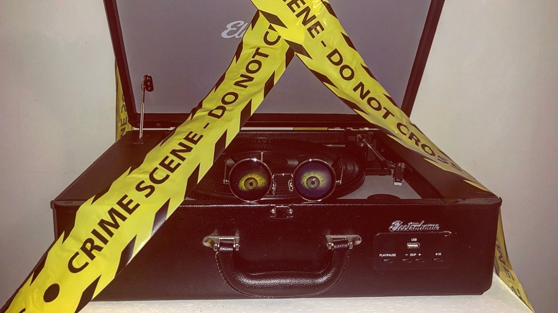 a record player with spooky glasses on and caution tape around it.