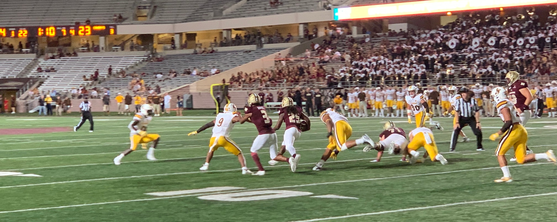 A Texas State player in a maroon jersey runs on a football field in between multiple Wyoming players in white and yellow uniforms at Jim Wacker Field in San Marcos, Texas with the fan and bands watching from the stands.
