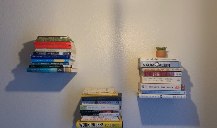 Three stacks of books on three floating shelves on a white wall with a large light bulb