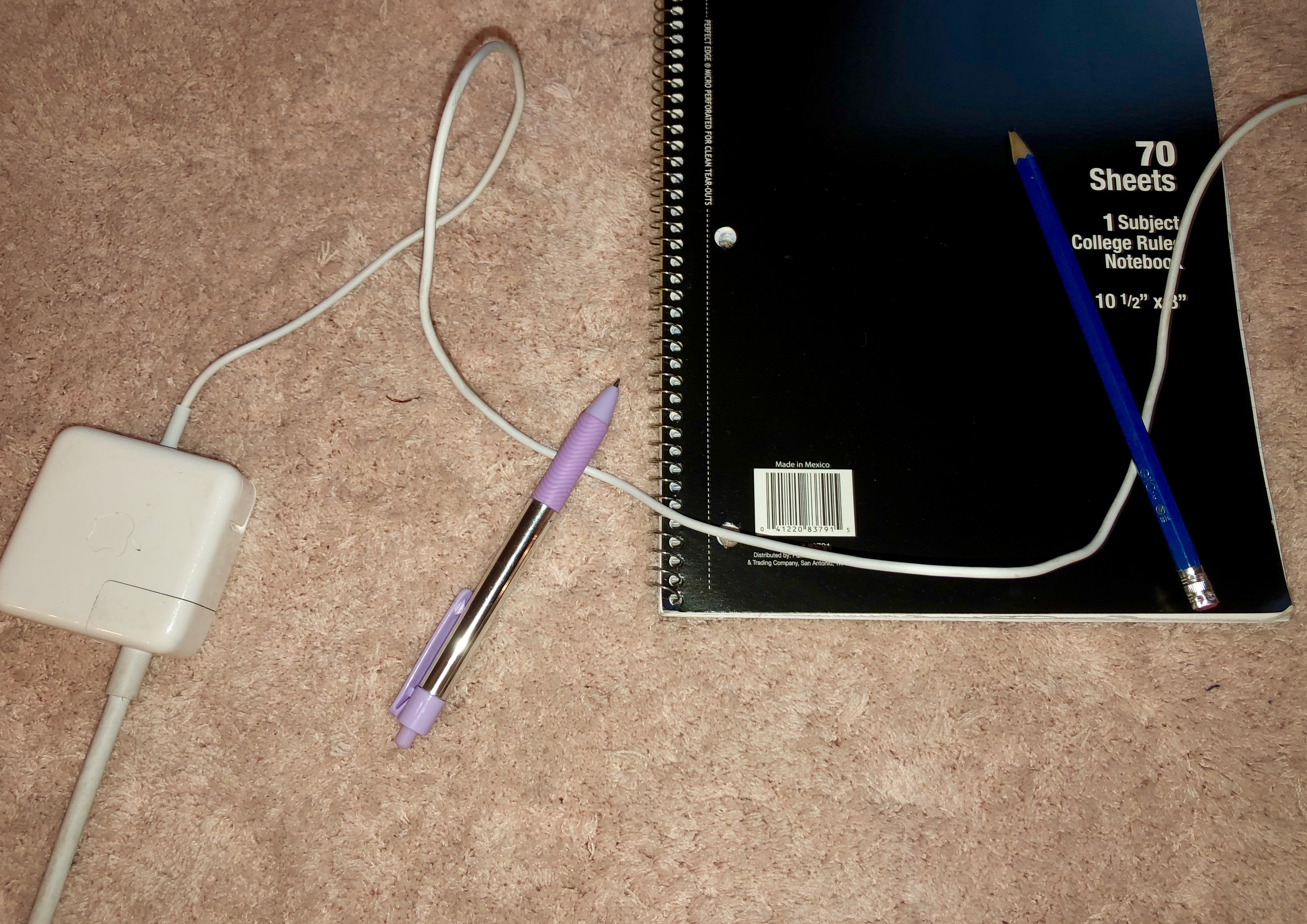 A white laptop charger next to a purple pen, black notebook and blue pencil.