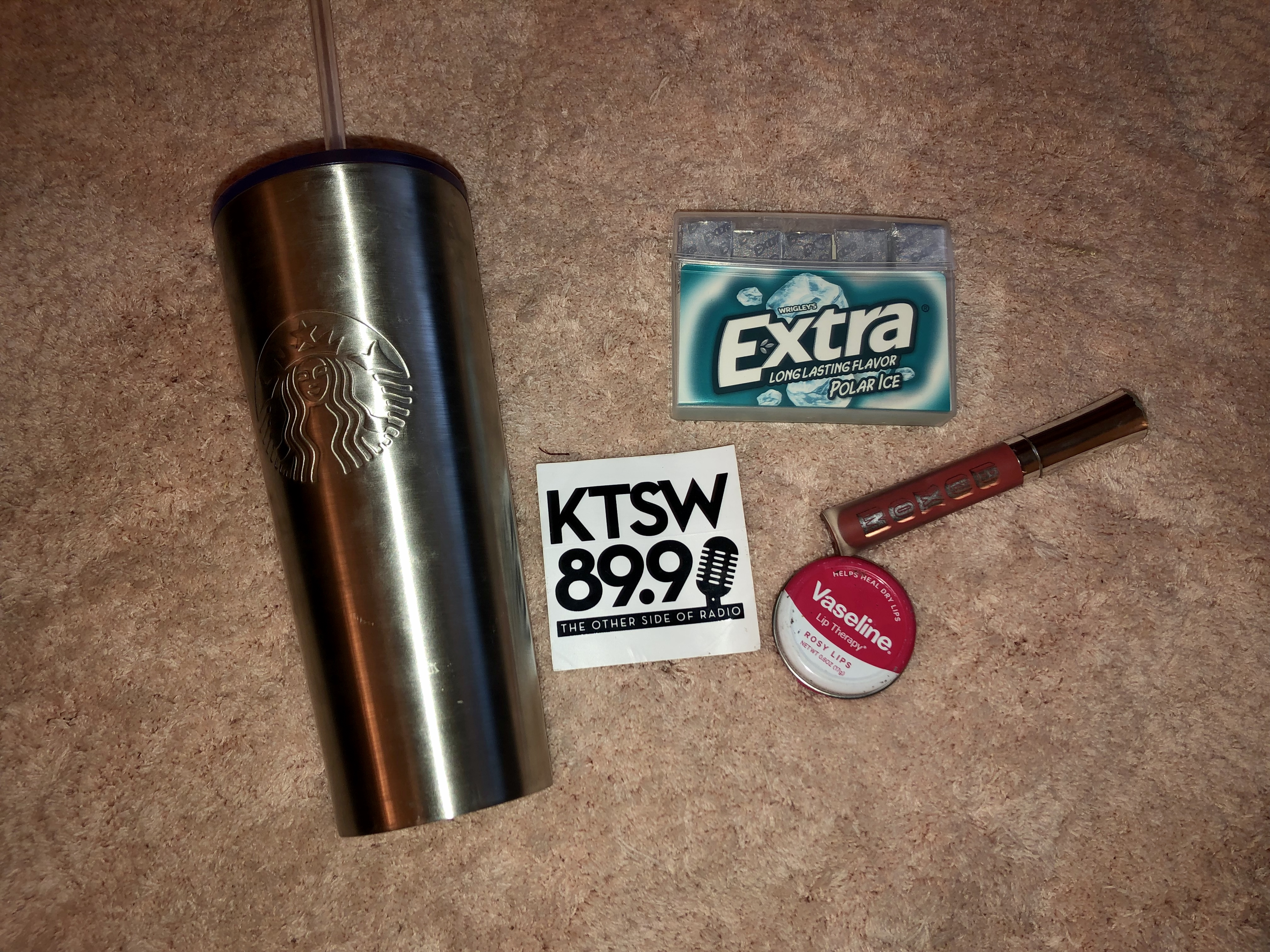 A silver Starbucks cup next to a white KTSW sticker, blue gum package, red lipgloss and pink chapstick