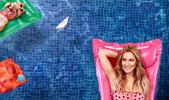 Caroline Flack floats in a pool smiling to promote the new season of Love Island