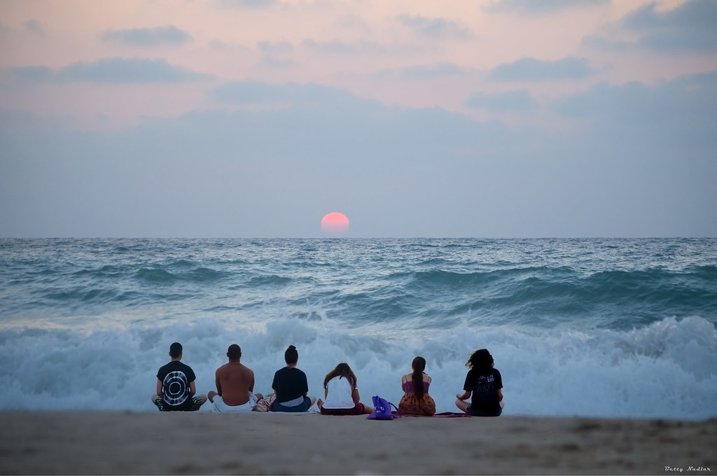 A group of six people on a beach at sunset.