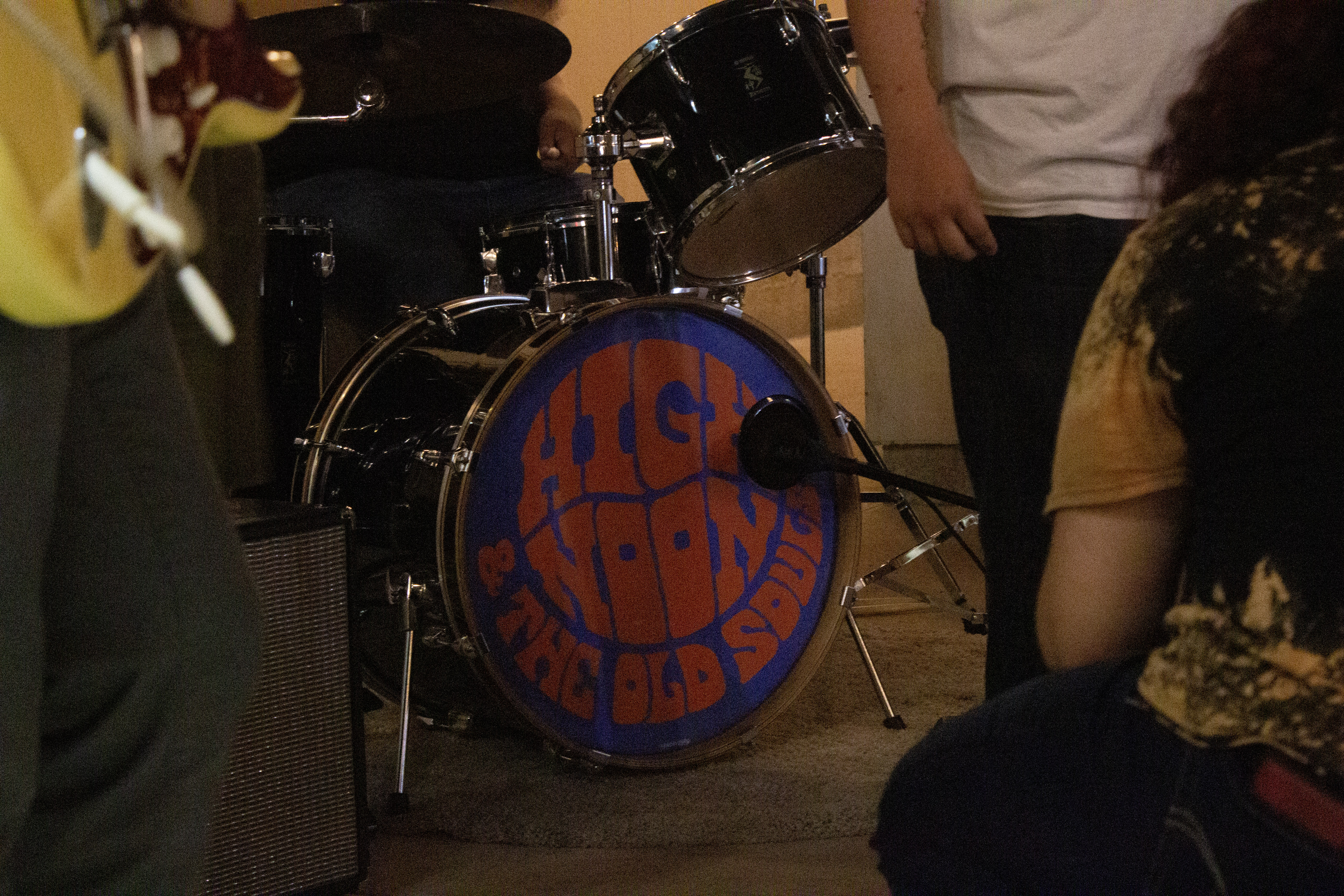 the photo is centered on the bass drum of the drum kist, featuring a logo of the band's name, High Noon and the Old Souls. Band members are gathered around the kit, setting up their respective instruments