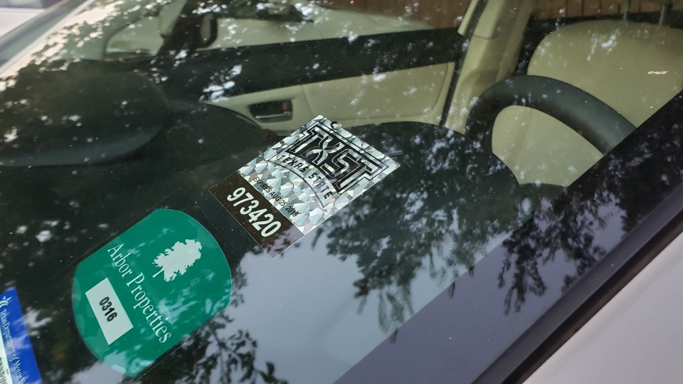A silver parking permit with the Texas State logo and hints of maroon is attached to a vehicle's windshield.