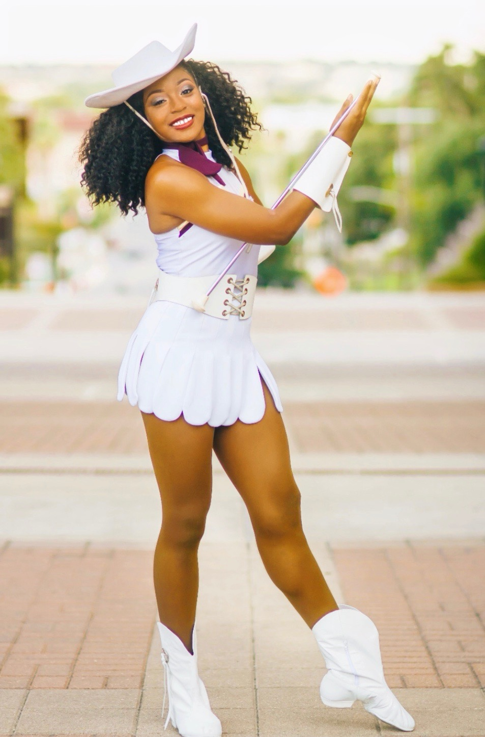 Ravyn Ammons posing standing up in her white Strutters uniform with white boots and a white hat.