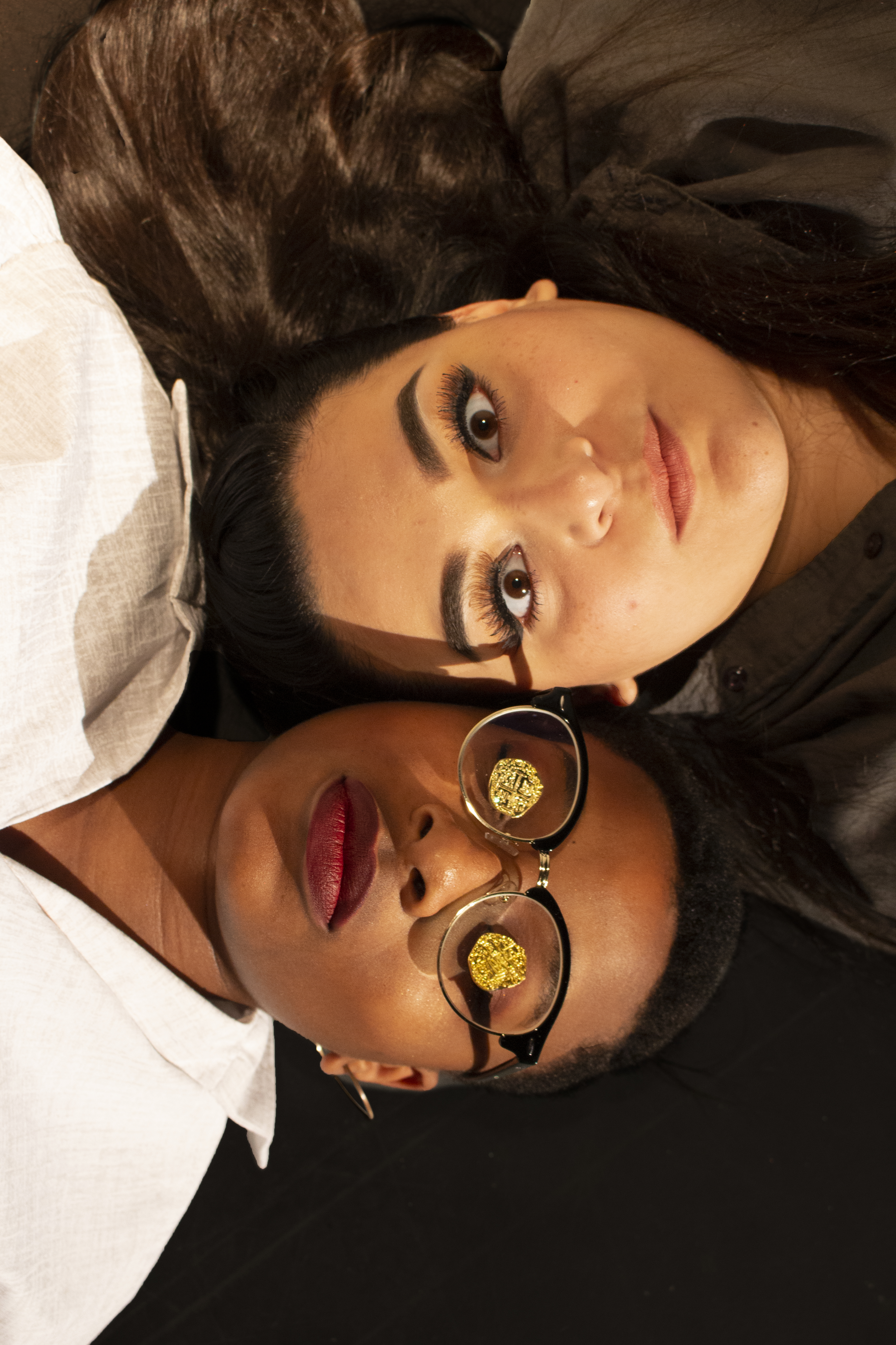 two girls laying side by side, one with coins over her glasses
