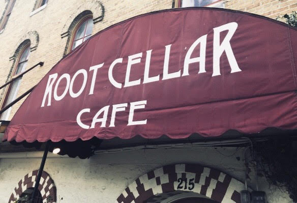 Root Cellar Cafe in white lettering on a red canopy outside the restaurant