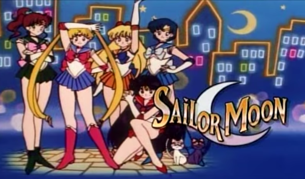 Sailor Jupiter, Sailor Moon, Sailor Venus,Sailor Mercury and Sailor Mars stand in their costumes each a school uniform of a skirt and shirt but different colors.